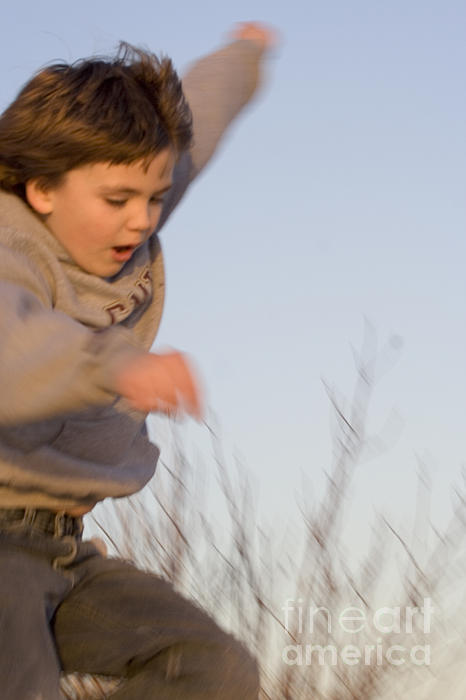 Boy Jumping Off Sand Dune Print by Christopher Purcell