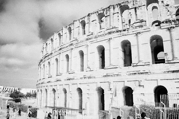 Entrance And Front Of The The Old Roman Colloseum Against Blue Cloudy Sky El Jem Tunisia Print by Joe Fox