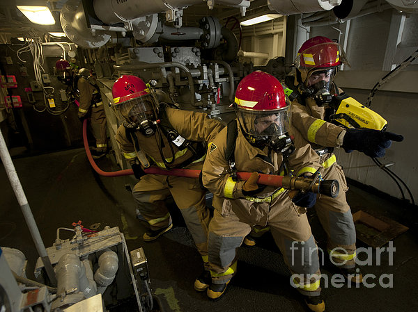 Firemen Combat A Simulated Fire Aboard Print by Stocktrek Images
