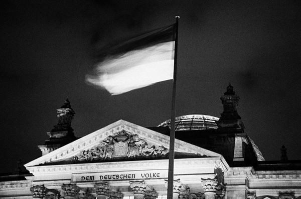 german flag flying fluttering on flagpole outside reichstag building Berlin Germany Print by Joe Fox