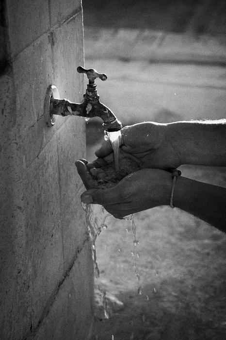 Hispanic Man Cupping Water And Washing Hands At Outdoor Tap Print by Joe Fox