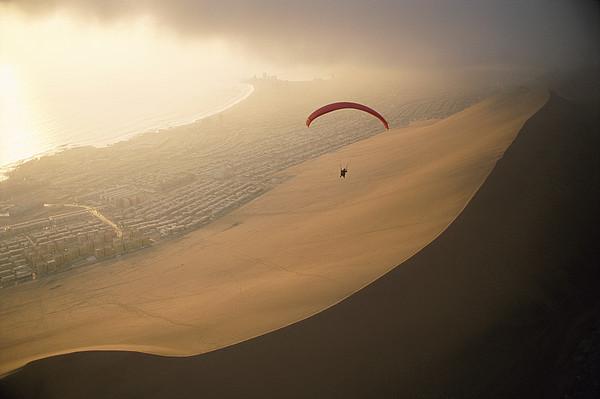 Ocean Gusts Keep A Paraglider Aloft Print by Joel Sartore