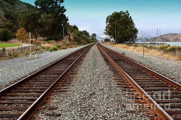 Railroad Tracks With The New Alfred Zampa Memorial Bridge And The Old Carquinez Bridge In Distance Print by Wingsdomain Art and Photography