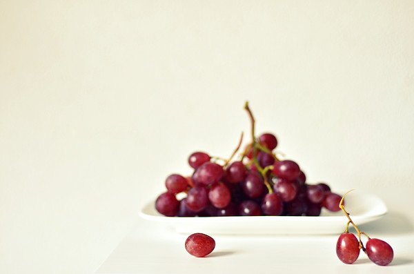 Red Grapes On White Plate Print by Photo by Ira Heuvelman-Dobrolyubova