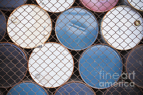 Rows Of Stacked Barrels Behind A Fence Print by Paul Edmondson