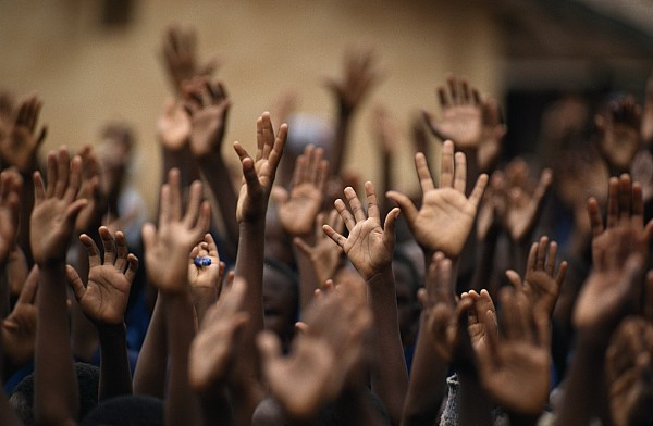 School Children Raise Their Hands Print by Lynn Johnson