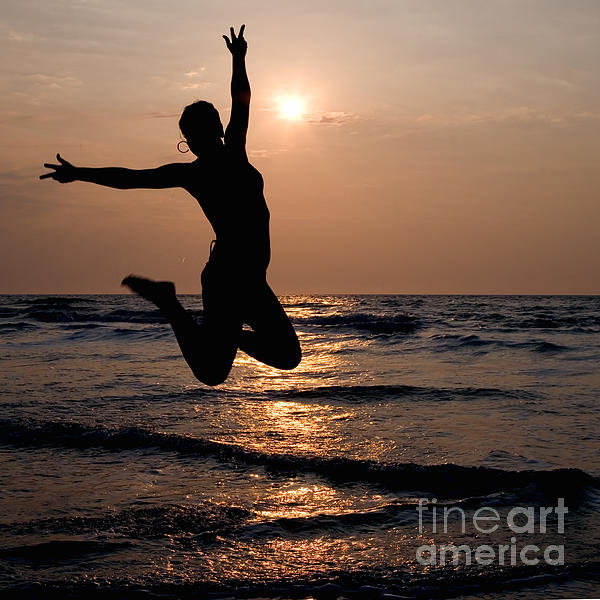 Silhouette Of A Girl Jumping In The Ocean At Sunset Print by William Langeveld