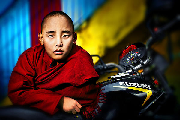 The Boy Monk In Red Robe Standing Beside A Motorcycle In A Buddh Print by Max Drukpa