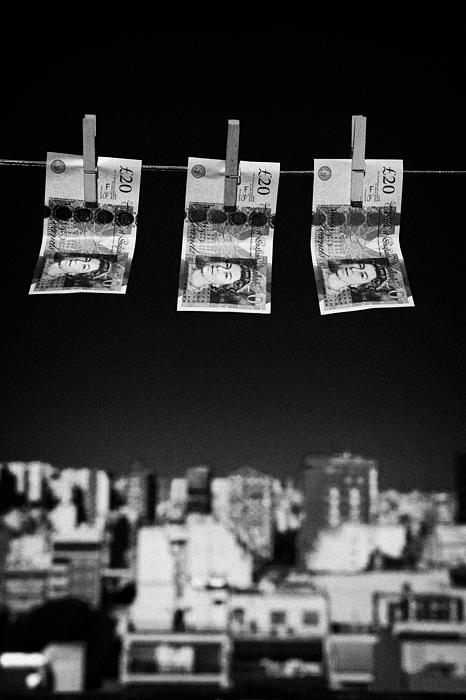 Three Twenty Pounds Sterling Banknotes Hanging On A Washing Line With Blue Sky Above A City Skyline Print by Joe Fox