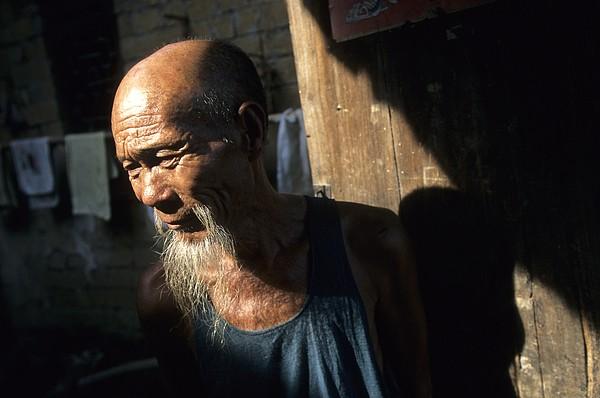 Village Elder At Doorway, Yangdi Print by Raymond Gehman