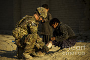 Physical Pain Posters - Airman Provides Medical Aid To A Local Poster by Stocktrek Images