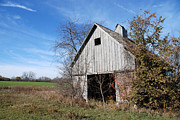 Decrepit Prints - An old rundown abandoned wooden barn under a blue sky in midwestern Illinois USA Print by Paul Velgos