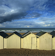 Coasts Prints - Beach huts under a stormy sky in Normandy. France. Europe Print by Bernard Jaubert
