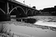 Sask Prints - broadway bridge over the south saskatchewan river in winter flowing through downtown Saskatoon Saska Print by Joe Fox