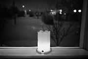 Candle Lit Prints - candle in the window looking out over snow covered scene in small rural village of Forget Saskatchew Print by Joe Fox