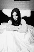 In Bed Photo Prints - Cold Early Twenties Woman Holding Hot Water Bottle Tightly In Bed In A Bedroom Print by Joe Fox