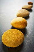 Stepping Prints - Diagonal Line of Brown Pebbles on Dark Background Print by Colin and Linda McKie
