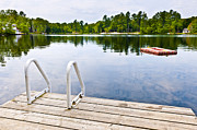 Green Trees Framed Prints - Dock on calm lake in cottage country Framed Print by Elena Elisseeva