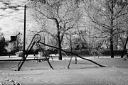 Sask Prints - empty childrens playground with hoar frost covered trees on street in small rural village of Forget  Print by Joe Fox