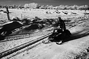 Conditions Framed Prints - man on snowmobile crossing frozen fields in rural Forget Saskatchewan Canada Framed Print by Joe Fox