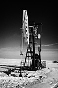Pumping Oil Framed Prints - oil pumpjack in winter snow Forget Saskatchewan Framed Print by Joe Fox