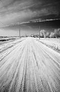 Winter Roads Framed Prints - snow covered road in small rural farming community village Forget Saskatchewan Canada Framed Print by Joe Fox