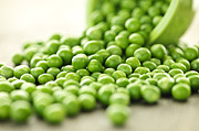 Pea Photos - Spilled bowl of green peas by Elena Elisseeva