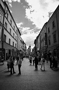 Polish City Framed Prints - Tourists On The Ulica Florianska Street Leading Down From City Gates To Old Town City Centre Krakow Framed Print by Joe Fox
