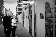 Berlin Germany Photo Prints - tourists read the history of the berlin wall at checkpoint charlie Berlin Germany Print by Joe Fox
