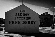 Irish Artists Prints - you are now entering free derry gable wall painting with petrol bomber mural in the background at free derry corner in the bogside area of Derry Londonderry Print by Joe Fox