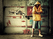 Adolescence Posters - Young man in hooded sweatshirt on grunge wall Poster by Michal Bednarek