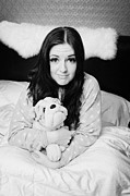 In Bed Photo Prints - Early Twenties Woman Holding Cuddly Dog Soft Toy In Bed In A Bedroom Print by Joe Fox