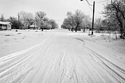 Snow Covered Village Prints - empty intersection on snow covered street in small rural farming community village Forget Saskatchew Print by Joe Fox