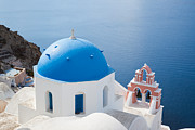 Greek Icon Posters - Iconic blue domed churches in Oia Santorini Greece Poster by Matteo Colombo