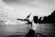 Smartphone Posters - man taking photos with smartphone during boat ride along the colorado river in the grand canyon Ariz Poster by Joe Fox