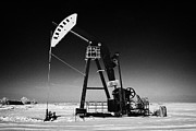 Sask Prints - oil pumpjack in winter snow Forget Saskatchewan Print by Joe Fox