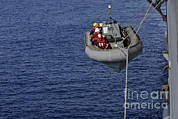 Inflatable Photos - Sailors Lower A Rigid-hull Inflatable by Stocktrek Images