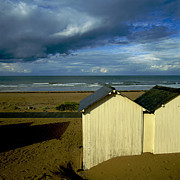 Architecture Prints - Beach huts under a stormy sky in Normandy. France. Europe Print by Bernard Jaubert