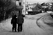 Snow Covered Street Framed Prints - Middle Aged Couple Walking Along Snow Covered Street With Sticks Kirkenes Finnmark Norway Europe Framed Print by Joe Fox