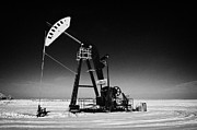 Pumpjack Posters - oil pumpjack in winter snow Forget Saskatchewan Canada Poster by Joe Fox