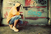 Hooded Figure Prints - Young man portrait on graffiti grunge wall Print by Michal Bednarek