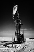 Pumping Oil Framed Prints - oil pumpjack in winter snow Forget Saskatchewan Canada Framed Print by Joe Fox