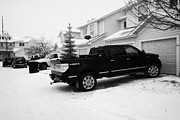 Snow Falling Prints - 4x4 pickup trucks parked in driveway in snow covered residential street during winter Saskatoon Sask Print by Joe Fox