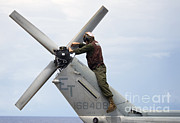 Scrutiny Photos - A Marine Conducts Maintenance by Stocktrek Images