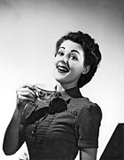 Perky Posters - A perky woman enjoys her cup of coffee. Poster by Underwood Archives