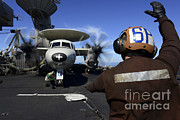 View Over Framed Prints - A Sailor Signals To Pilots Of An E-2c Framed Print by Stocktrek Images
