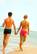 Couple In Arms Posters - A teenage couple walking on the beach Poster by Michal Bednarek