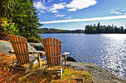 Trees Photos - Adirondack chairs at lake shore by Elena Elisseeva
