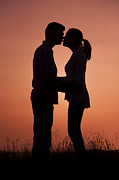 Woman In Summer Meadow Posters - Affectionate Couple At Sunset In Profile  Poster by Lee Avison