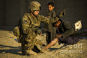 Helping Prints - Airman Provides Medical Aid To A Local Print by Stocktrek Images
